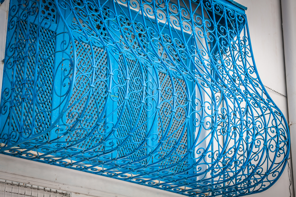Beautiful ornamental blue windows on a white wall so typical for Tunisia